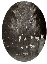 President Coolidge lighting the first White House Christmas tree. Notice the candles use to light the tree.